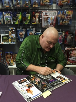 King Kong Bundy signing his entry in the WWE Encyclopedia, Vol. 2
