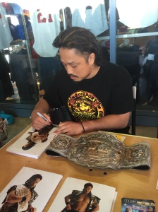 Goto signing w/Intercontinental Championship beside him